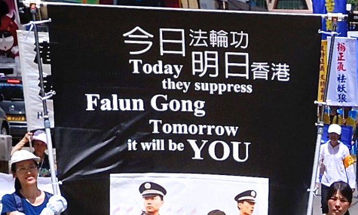 Participants in a parade on the afternoon of June 23, 2013 in Hong Kong carry a banner warning that the suppression of the rights of Falun Gong practitioners in Hong Kong can spread to others. Speakers at a rally following the parade condemned Hong Kong's chief executive for being a member of the Chinese Communist Party and responsible for campaigns aimed at suppressing Falun Gong practitioners and democracy activists. (Song Xianglong/Epoch Times)