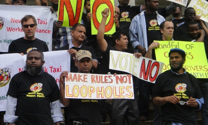 Protesters hold signs and shout outside the New York City Hall on June 11 to urge the city administration to turn down new rules by the Taxi and Limousine Commission. (Courtesy New York Taxi Workers Alliance)