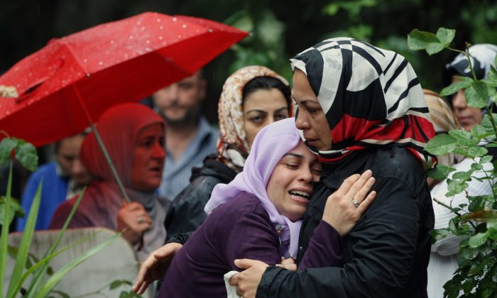 Mourning relatives cry during the burial of one of the 46 victims killed by explosions in the Turkish border town Reyhanli, May 12, 2013. (AP Photo/Burhan Ozbilici)