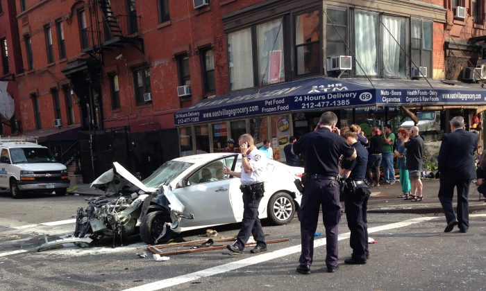 In this photo provided by Jan Sichermann, authorities work the scene where eight people were hurt, several of them seriously, after a car jumped a curb and slammed into a 24-hour grocery store, Wednesday, June 19, 2013, in New York. (Jan Sichermann/AP Photo)