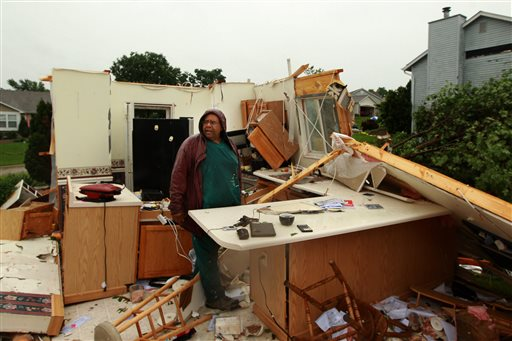 """Wilburn Shaw looks for personal items in the remains of his kitchen in his home on Saturday, June 1, 2013, after Friday night's storm that passed through St. Charles, Mo., area.  The storm toppled cars and left commuters trapped on an interstate highway as it bore down during Friday's evening rush hour near Oklahoma City. The National Weather Service reported """"several"""" tornadoes rolled in from the prairie, terrifying towns along their paths.  (AP Photo/St. Louis Post-Dispatch, Huy Mach)"""