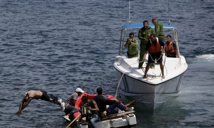 In this June 4, 2009 file photo, Cuban coast guards, right, stop seven men trying to migrate illegally to the U.S. on a foam raft near Havana's Malecon.  No one was arrested, according to police. (AP Photo/Javier Galeano)