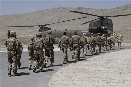 NATO solders walk towards a Chinook helicopter after a ceremony at a military academy on the outskirts of Kabul, Afghanistan, Tuesday, June 18, 2013.  (AP Photo/Rahmat Gul)