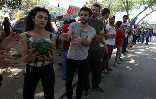 Protesters form a human chain to carry watermelons at the Gezi Park of Taksim Square in Istanbul, Monday, June 10, 2013. Turkey's Prime Minister Recep Tayyip Erdogan said he would meet with a group of protestors on June 12, as the protests entered their 11th day on June 10. (AP Photo/Thanassis Stavrakis)