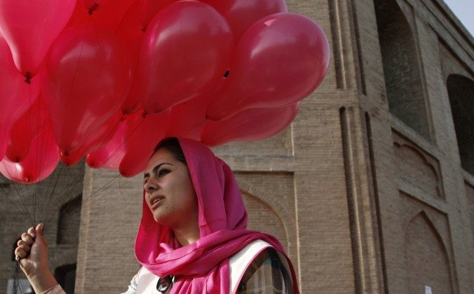 An Afghan woman holds a portion of some 10,000 pink balloons handed out by artists and activists in Kabul, Afghanistan, Saturday, May, 25, 2013. Development in Afghanistan cannot be imposed or bestowed from without. (AP Photo/Ahmad Jamshid)