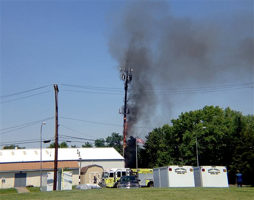 A cellphone tower burns at the Bensalem Municipal complex Friday, June 21, 2013 in Bensalem, Pa. A 75-foot-tall cellphone tower caught fire on Friday while work was being done on it and was leaning, prompting the evacuations of nearby homes. It was later removed safely. (AP Photo/Bucks County Courier Times, Jo Ciavaglia)