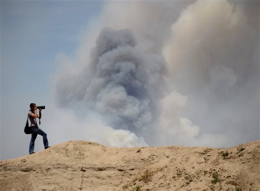 A photographer takes photos of the Black Forest Fire as it burns out of control for a second straight day near Colorado Springs, Colo. on Wednesday, June 12, 2013. Three Colorado wildfires fueled by hot temperatures, gusty winds and thick, bone-dry forests have together burned dozens of homes and led to the evacuation of more than 7,000 residents and nearly 1,000 inmates at medium-security prison. (AP Photo/Bryan Oller)