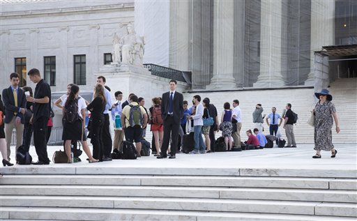 People wait outside the Supreme Court in Washington as key decisions are expected to be announced Monday, June 24.  The court made an unexpected announcement on June 25, when it ended Section IV of the Voting Rights Act. (AP Photo/J. Scott Applewhite)