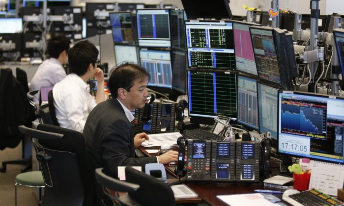 Takashi Yamada (R) a government-bond trader at major brokerage Daiwa Securities Co., monitors screens at his bond trading section in Tokyo on June 5, 2013. Until a couple of months ago, Yamada had one of the most genteel jobs in Japan. Now, his days are so harried he doesn't have time to eat lunch. (Shuji Kajiyama/AP)