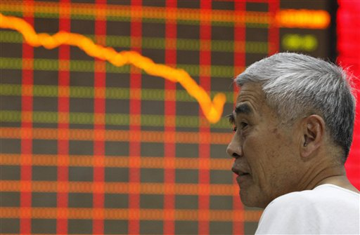 A stock investor watches a board displaying stock prices at a brokerage house in Huaibei in central China's Anhui province Monday June 24, 2013. Numerous rumors about bank defaults and glitches as well as bad economic data have pushed stocks in China in bear market territory. (AP Photo)