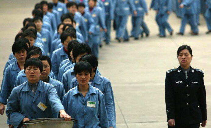 Prisoners walk beside a police escort during a prison open day in Nanjing, 2005. Western companies launched investigations recently on claims that headphones and other electronics they bought were made in a Chinese forced labor camp. (STR/AFP/Getty Images)
