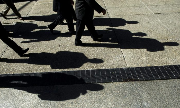 Businessmen cast their shadows as they walk in Toronto's financial district in this file photo. (THE CANADIAN PRESS/Nathan Denette)