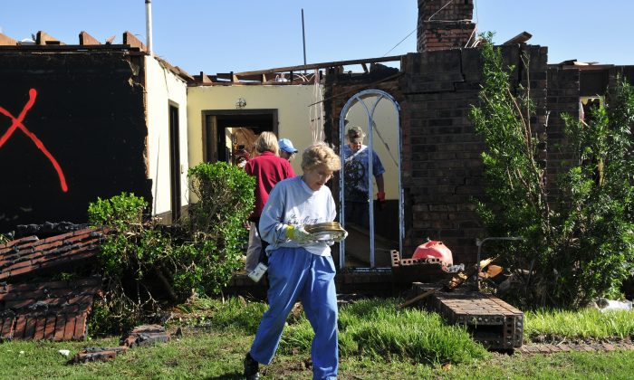 Rilma Hulett carries a dish set from her friend Bobbie Steenbergen's home that was destroyed by the tornado that swept through Central Oklahoma Friday afternoon on Saturday June 1, 2013 in El Reno Okla. Emergency officials set out Saturday morning to see how much damage a violent burst of thunderstorms and tornadoes caused as it swept across the Midwest overnight.  (AP Photo/Nick Oxford)