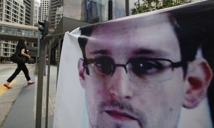A banner of Edward Snowden, the former CIA employee who leaked top-secret documents about U.S. surveillance programs, is displayed at Central, Hong Kong's business district, Thursday, June 20, 2013.  Snowden has been charged with espionage on June 21. (AP Photo/Kin Cheung)
