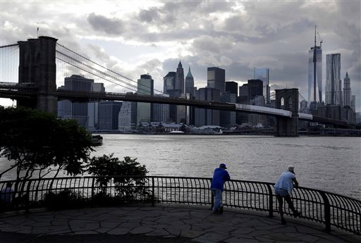 Pedestrians looks across the East River at the lower Manhattan skyline in New York, Tuesday, June 11, 2013. Mayor Michael Bloomberg said the recent bankruptcy declared by Detroit could happen elsewhere at a press conference on Aug. 6. (AP Photo/Seth Wenig)