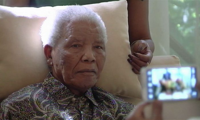 In this file image taken from video, the ailing anti-apartheid icon Nelson Madela is filmed Monday April 29, 2013, more than three weeks after being released from hospital.  The 94-year-old anti-apartheid leader has been hospitalized for about three weeks with a reoccurring lung infection and South African officials have now deemed his condition critical. (SABC TV/AP)