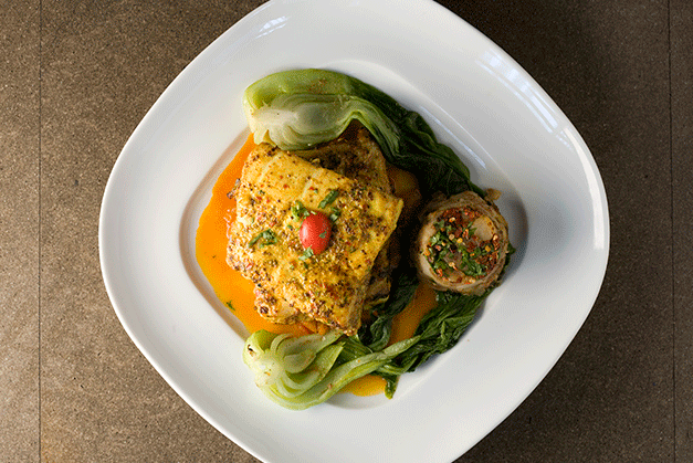 Served at Tamarind, the Tawa Machli, a filet of halibut rubbed with black pepper, coarse-grain mustard, dry red chilies, cumin seeds and lemon juice, pan-seared, and served with browned cipollini onions and tomato. (Courtesy of Tamarind)