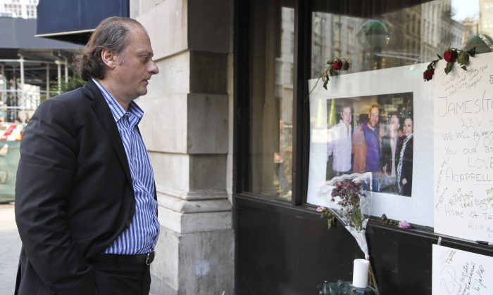 Sergio Acappella looks at a shrine set up for the late Sopranos actor James Gandolfini outside of his Tribeca restaurant on June 24. Gandolfini was a regular at Acappella. (Amelia Pang/Epoch Times)