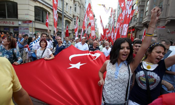Protesters shout slogans as they hold a Turkish flag during the third day of nationwide anti-government protest at the Taksim square in Istanbul, June 2, 2013. Fierce clashes have followed a police crackdown on a peaceful gathering, as protesters denounced what they see as Prime Minister Recep Tayyip Erdogan's increasingly authoritarian style. (AP Photo/Thanassis Stavrakis)