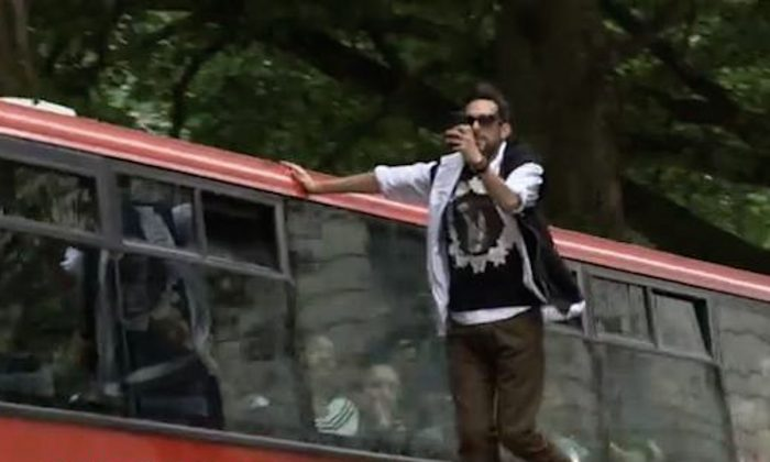 Illusionist Dynamo seems to float magically alongside a double-decker bus in London, England on June 24, 2013. (Screenshot/YouTube)