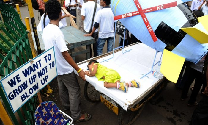 A child of an Indian protestor sleeps on a handcart carrying a paper mache replica of an atomic bomb during a rally in Mumbai on Aug. 6, 2010, to mark the 65th anniversary of the world's first atomic bombing on Hiroshima. Japan, the only country that has ever been attacked with atomic bombs—first on Aug. 6, 1945 in Hiroshima, and three days later in Nagasaki—has pushed for the abolition of this weapon of mass destruction ever since. (Indranil Mukherjee/AFP/Getty Images)