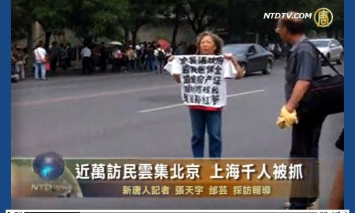 A petitioner holds up a T-shirt with slogans of protest written on it. Thousands of petitioners are reported to have gathered in Beijing on Friday May 31, as the anniversary of June 4 approaches. The authorities packed them into buses. (Screenshot of NTD Television via The Epoch Times)