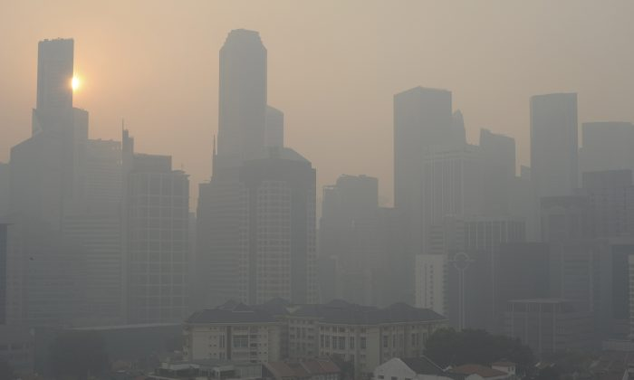 The sun rises over the Singapore Central Business District, or CBD, skyline as a haze envelopes the city on Thursday, June 20, 2013. The smoky haze triggered by forest fires in neighboring Indonesia has caused air pollution to briefly hit its worst level in nearly 16 years in Singapore. (AP Photo/Joseph Nair)