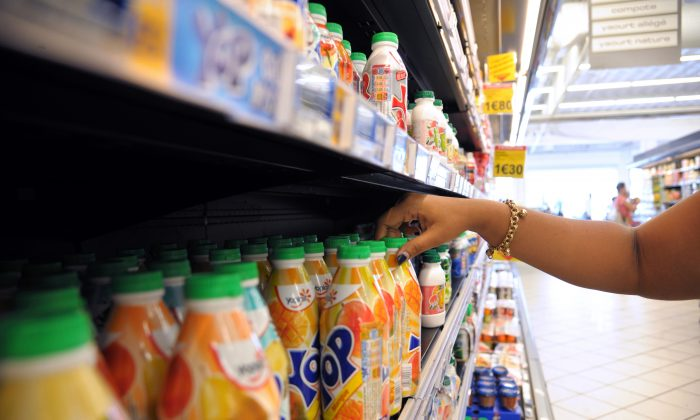 A file photo of a woman choosing some yogurt products in a supermarket of Fort-de-France, in the French Caribbean island of La Martinique on March 30, 2013. A small yogurt drink can contain 32 grams of sugar. Detoxes that help cut out addictive foods, processed foods, sugars, and dairy—the foods that commonly cause inflammation in the body—help many people feel better. (Jean-Michel Andre/AFP/Getty Images)