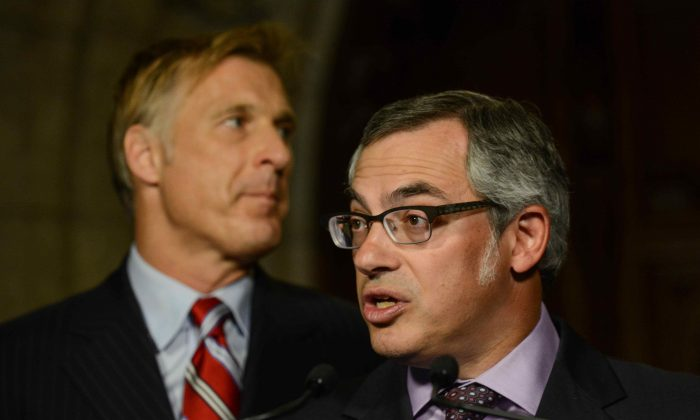 Treasury Board President Tony Clement announces changes to public sector sick leave as Maxime Bernier, Minister of State for Small Business and Tourism, looks on in the foyer of the House of Commons on Parliament Hill Monday. (Matthew Little/The Epoch Times)