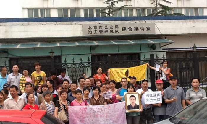 """Petitioners from across China stand outside a building affiliated with the Beijing Public Security Bureau on July 1, 2013, the 92nd anniversary of the founding of the Chinese Communist Party. They held signs and shouted out slogans like """"Down with corrupt officials."""" (Human Rights Campaign in China)"""