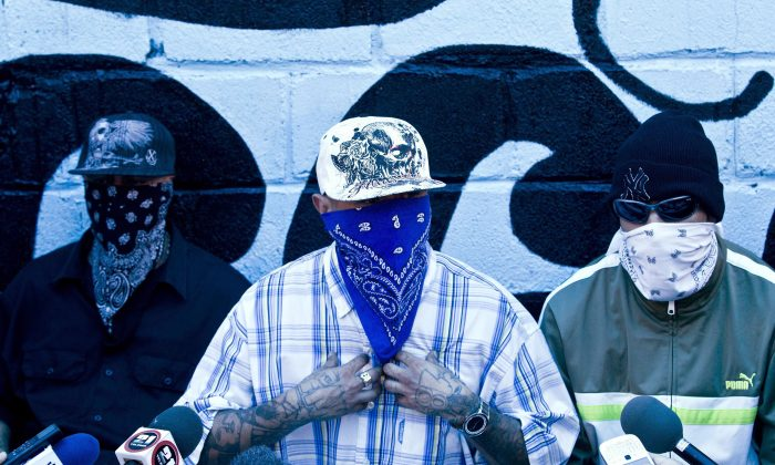 Masked members of the Mara 18 gang give a press conference inside the San Pedro Sula Prison in Honduras, on May 28, 2013. Honduras' largest and most dangerous street gangs have declared a truce, offering the government peace in exchange for rehabilitation and jobs. A Mara Salvatrucha spokesman says the gang and a rival known as 18th Street will commit to zero violence and zero crime in the streets as first step show of good faith. (AP Photo/Esteban Felix)