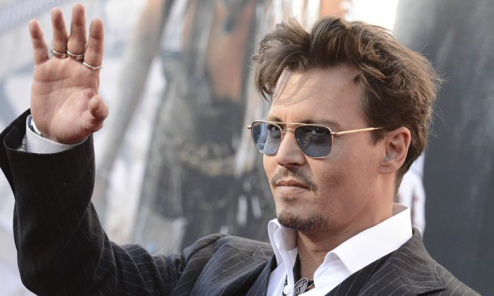 """In this Saturday, June 22, 2013 photo, actor Johnny Depp arrives at the world premiere of """"The Lone Ranger"""" at Disney California Adventure, in Anaheim, Calif.  The Golden Globe-winning actor plays iconic Native American, Tonto, in the upcoming Disney reboot opening July 3. He said his children, Lily-Rose, 14, and Jack, 11, can't wait to see it. (Photo by Dan Steinberg/Invision/AP)"""