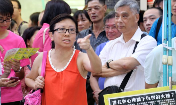 """A July 14, 2013 photo of Lam Wai Sze, a Hong Kong female teacher who spoke in defense of Falun Gong. She was recorded in a video that was later spliced to show her as the aggressor, which many of Lam's supporters have called """"the Chinese Communist Party's slander."""" (Pan Zai Shu/Epoch Times)"""