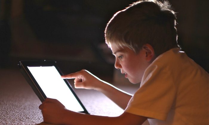 A young boy uses a tablet computer. A plan in the U.K. to offer parents a pornography filter through their ISP is garnering criticism for censorship implications but is necessary to protect children, argues Canadian MP Joy Smith. (Christopher Furlong/Getty Images)