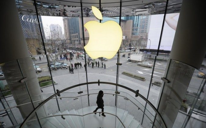 A customer walks under an Apple logo at an Apple store in Shanghai on Feb. 22, 2012. A supplier for Apple with factories in Shanghai has been found to be in violation of labor, environmental, and safety laws and regulations says a report by China Labour Watch. (PETER PARKS/AFP/Getty Images)