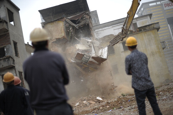 Workers on demolition orders look at a construction being taken down in Yangji village, Guangzhou, south China's Guangdong province on March 21, 2012. Recently a couple in Shandong were dragged out of bed so their house could be house demolished in the middle of the night, according to Chinese media reports. (STR/AFP/Getty Images)