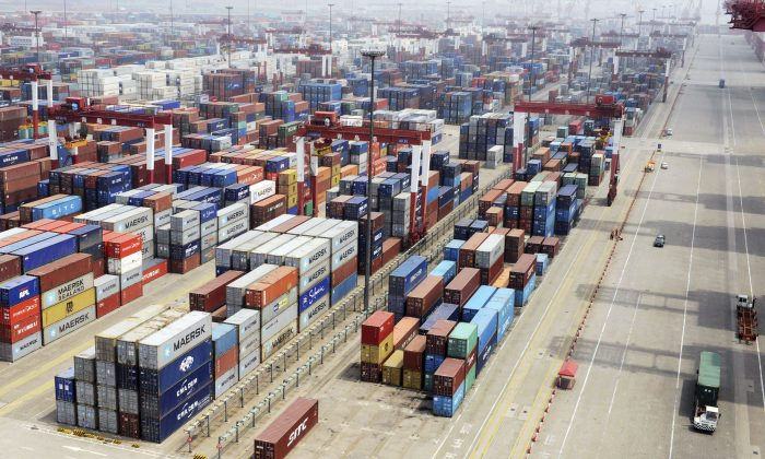 Containers are piled at a port in Qingdao in eastern China's Shandong Province on July 10, 2013. China reported Wednesday, July 10, 2013 that imports and exports both fell abruptly in June. The statistics are a new sign of weakness in the world's second-largest economy. (AP Photo)