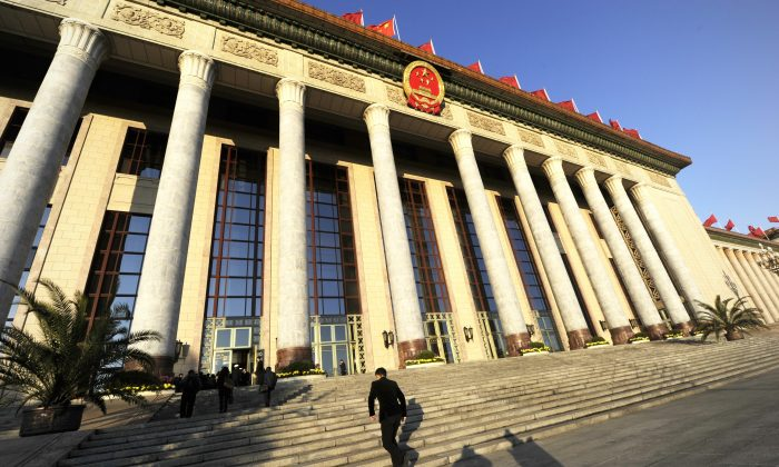A security guard walks up steps into the Great Hall of the People before the closing of the 18th Communist Party Congress in Beijing on 14 Nov. 2012. The central government has ordered a nationwide audit of local government debt. (Wang Zhao/AFP/Getty Images)