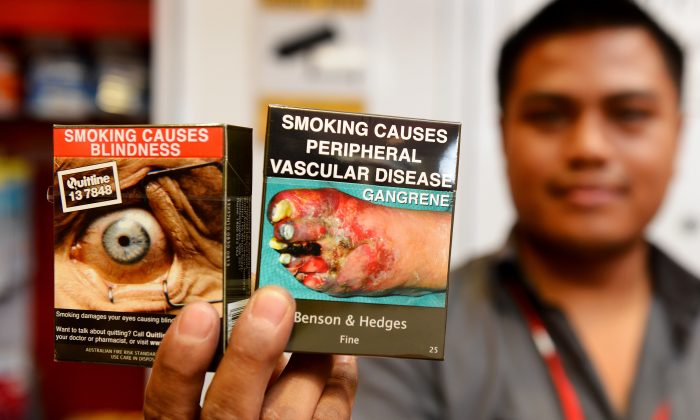 Bookshop supervisor Sanjit Amatya holds packaged cigarettes that have to be sold in identical olive-brown packets bearing the same typeface and largely covered with graphic health warnings in Sydney, Australia on December 1, 2012. The country passed a world-first law forcing tobacco companies to sell cigarettes in identical packets with the health warnings. (William West/AFP/Getty Images)