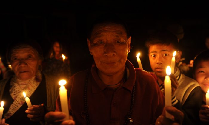 Tibetans-in-exile take part in a candlelight vigil in Kathmandu, India, on Feb. 13, 2013. A Chinese official has told a German news magazine that he will publish a book about the Party's policies in Tibet. (Prakash Mathema/AFP/Getty Images)