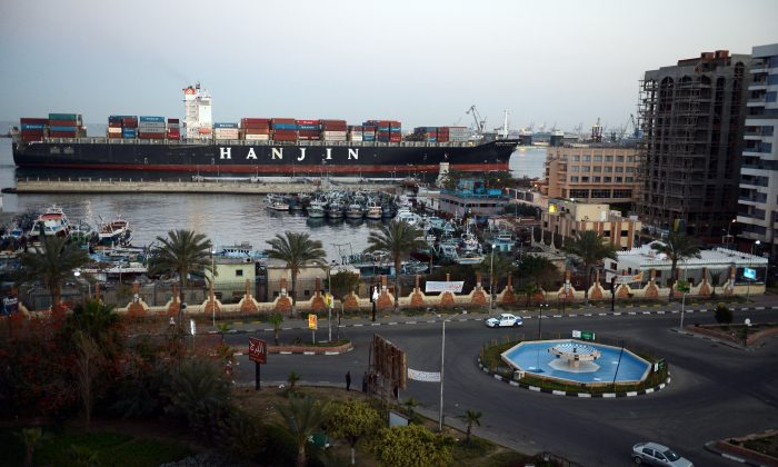 A container ship sails down the Suez Canal in the Egyptian city of Port Said on March 9, 2013. Traffic in the Suez Canal, a vital waterway for global commerce, has not been disrupted by demonstrations in Egypt. (Khaled DesoukiAFP/Getty Images)