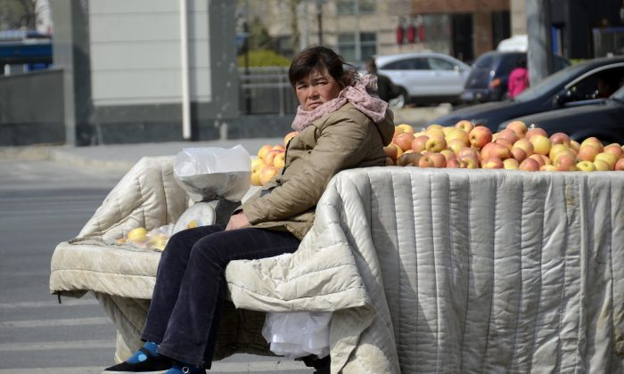 A street vendor in Beijing sits in a trailer filled with apples on April 14, 2013. Vendors like this are often harassed or beaten by Chengguans, thugs employed by city governments to enforce municipal regulations. (Wang Zhao/AFP/Getty Images)