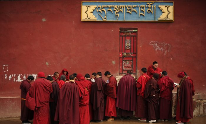 This photo taken on April 5, 2013 shows Buddhist monks collecting leaflets at Seda Monastery, the largest Tibetan Buddhist school in the world, in Sichuan Province, an area of China with many Tibetans. Chinese authorities recently opened fire on Tibetans celebrating the birthday of the Dalai Lama, according to a Tibetan human rights group. (Peter Parks/AFP/Getty Images)