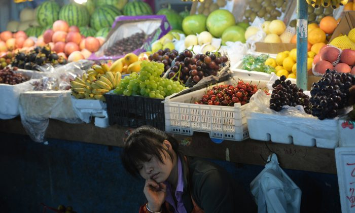 A fruit vendor takes a nap at a market in Shanghai on June 9, 2013. (Peter Parks/AFP/Getty Images)