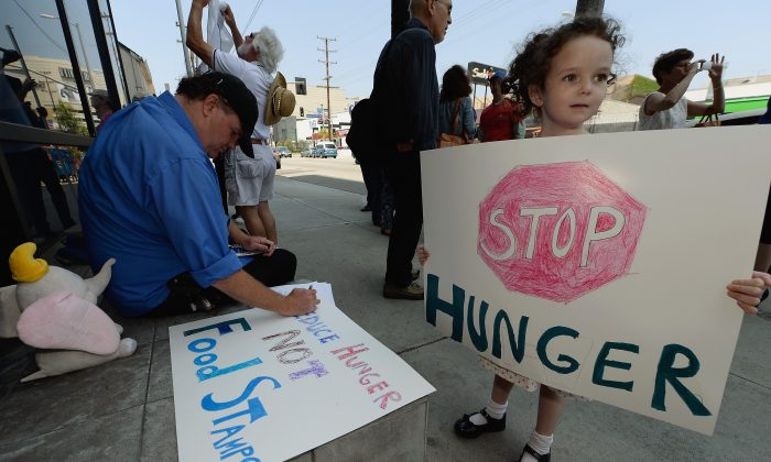A 5-year-old girl holds a sign next to her father (L) and other activists in front of Rep. Henry Waxman's office in Los Angeles, June 17. The protestors were asking the congressman to vote against a House farm bill that would have reduced federal spending on food stamps and other services for the poor.  (Kevork Djansezian/Getty Images)