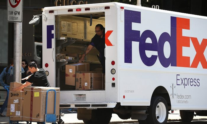 FedEx workers unload packages from a delivery truck on June 19 in San Francisco.  FedEx is among many companies and local governments that have been challenged over employee job classifications. (Justin Sullivan/Getty Images)
