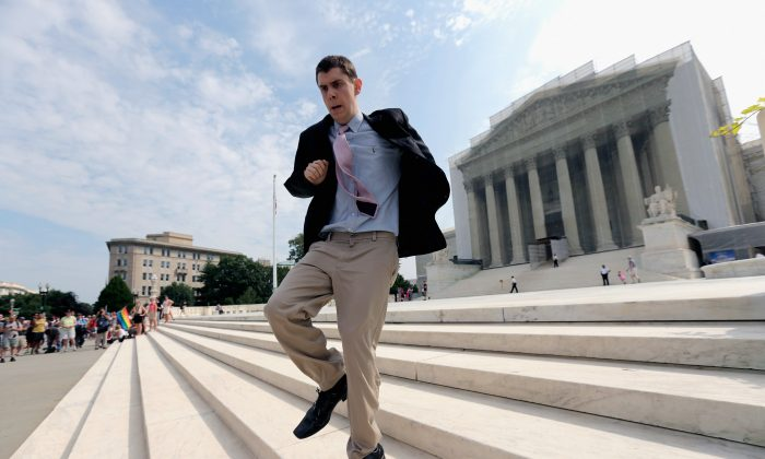 Intern Dan Stein runs with news of a recent ruling in front of the U.S. Supreme Court building in Washington, D.C., June 24. Recent statistics show close to two-thirds of students from the graduating Class of 2013 worked as interns, 47.8 percent of them for free. (Win McNamee/Getty Images)
