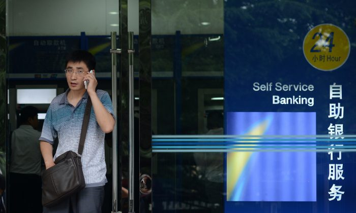 A man talks on a mobile phone at the entrance of a bank in Beijing on June 25, 2013. That morning the Chinese stock market tumbled 3.80 percent, extending the previous day's hefty losses as traders fretted over a liquidity crisis in the country's banking system. (Wang ZhaoAFP/Getty Images)