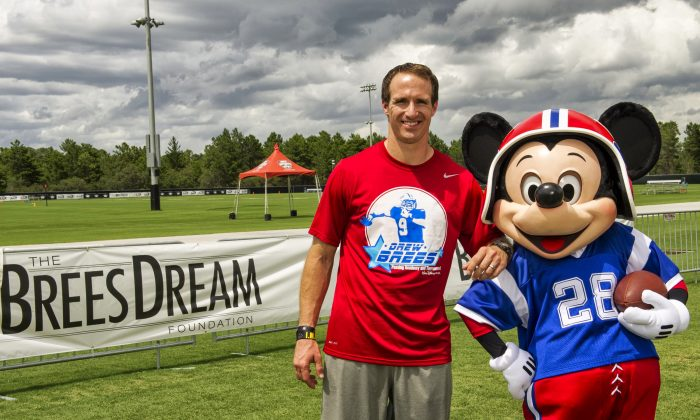 In this handout photo provided by Disney Parks, New Orleans Saints All-Pro quarterback Drew Brees poses with Mickey Mouse at ESPN Wide World of Sports Complex at Walt Disney World on June 26, 2013 in Lake Buena Vista, Florida. (Ali Nasser/Disney Parks via Getty Images)