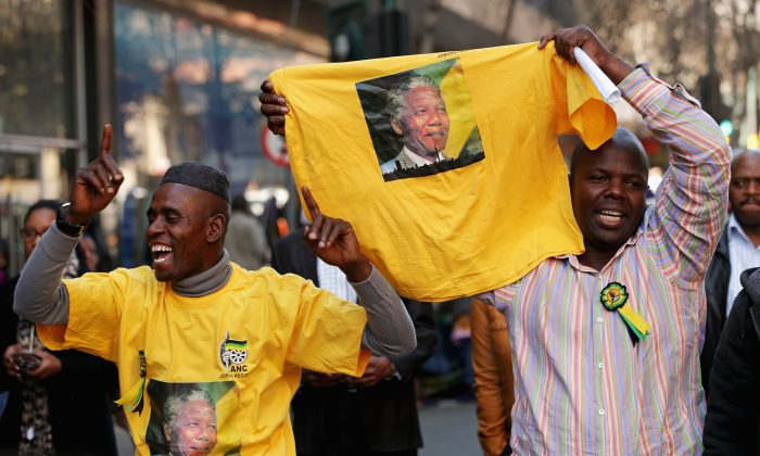 People pray and sing songs of support for former South African President Nelson Mandela during an African National Congress-sponsored prayer rally outside ANC headquarters July 2, 2013, in Johannesburg, South Africa.   Americans tend to connect Nelson Mandela with Martin Luther King, but according to one historian, Mandela has more in common with George Washington. (Chip Somodevilla/Getty Images)